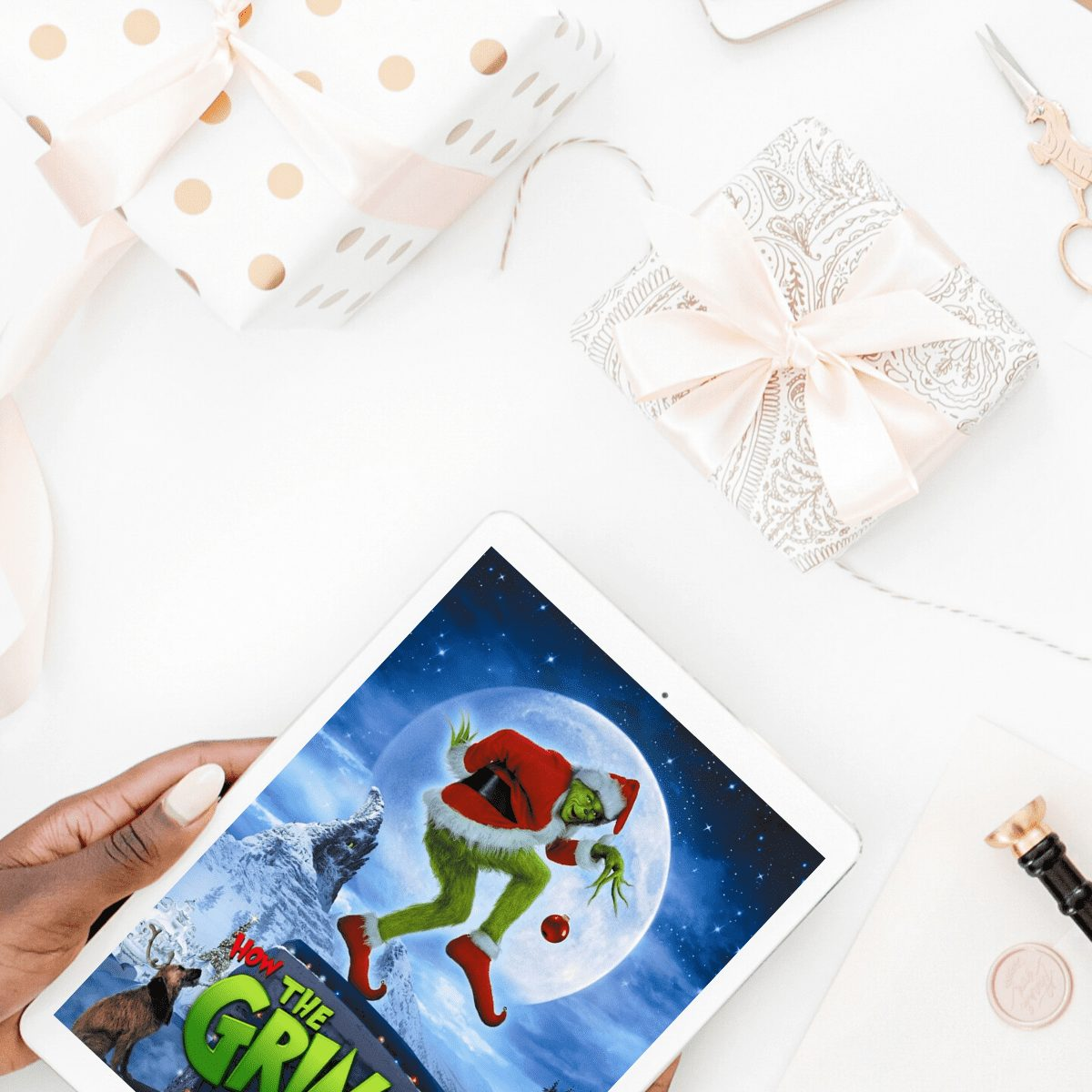 the grinch movie cover on an iPad surrounded by Christmas wrapped gifts
